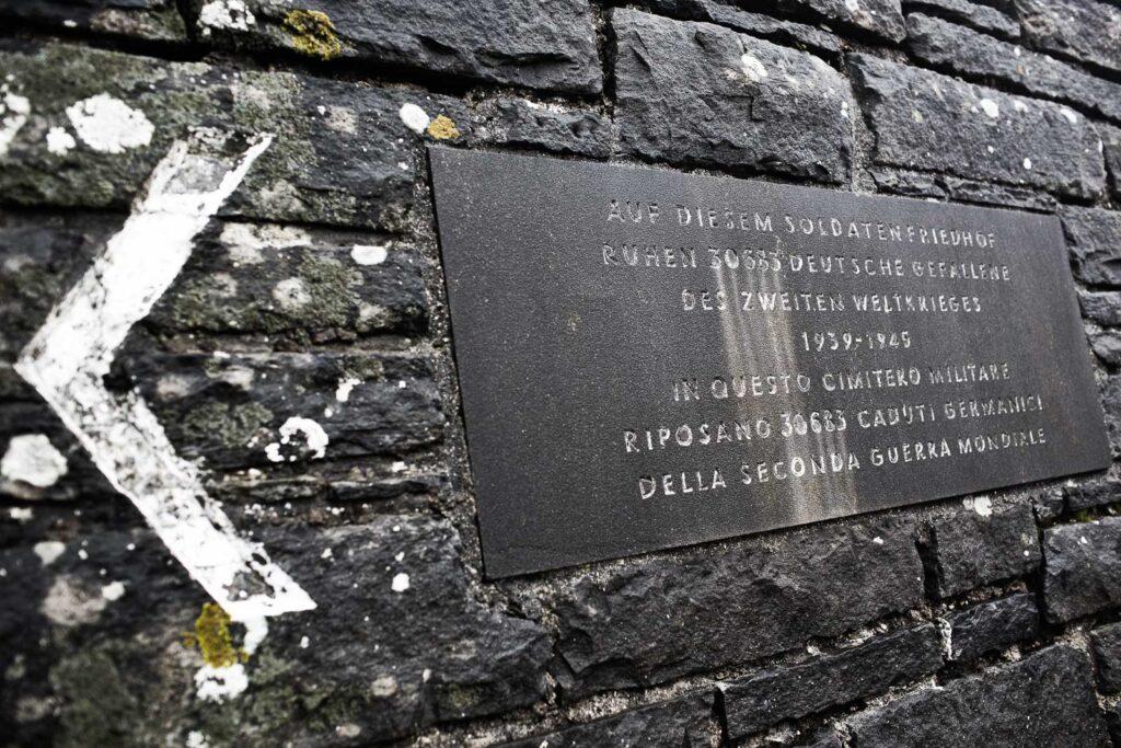 Iscrizione sul muro perimetrale del cimitero militare germanico del Passo della Futa